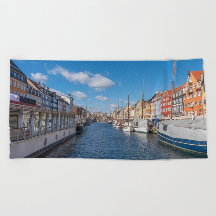 Nyhavn Canal under a blue sky with some clouds Beach Towel