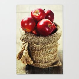 Burlap sack with apples on a wooden table Canvas Print