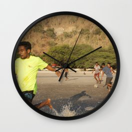 Timorese people play football in Areia Branca beach Wall Clock