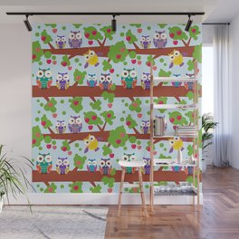 bright colorful owls on the branch of a tree with red apples on blue background Wall Mural