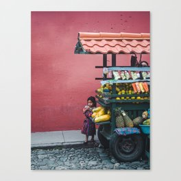 Young Guatemalan girl in traditional Mayan dress watches the street from behind a fruit stall cart Canvas Print