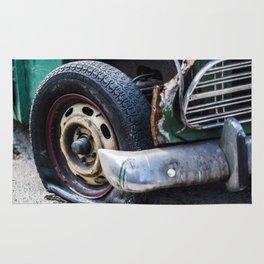 Flat tire on smashed vintage car Rug