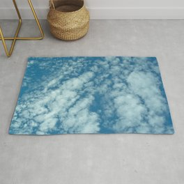 Fluffy clouds in a blue sky Rug
