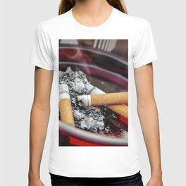 A ruby-colored glass ashtray contained three used cigarette butts along with their ashes A healthcar T-shirt