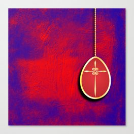 Gold cross in red egg hanging against a rich red and purple Canvas Print
