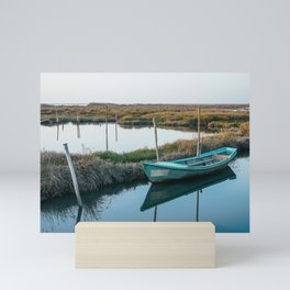 Weathered and abandoned small boat close to shore in peaceful lagoon on bright day. Mini Art Print