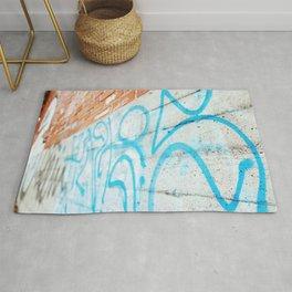 Blue graffiti on concrete wall Rug