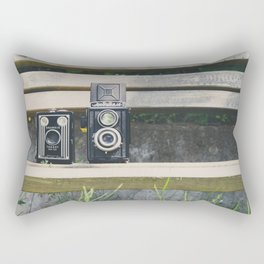 two vintage cameras sitting on a park bench ... Rectangular Pillow