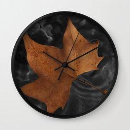 Leaf on dark water Wall Clock