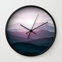 dark blue mountain landscape with fog and a sunrise and sunset Wall Clock