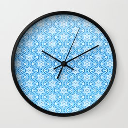wintery symmetrical pattern - snowflakes on blue Wall Clock