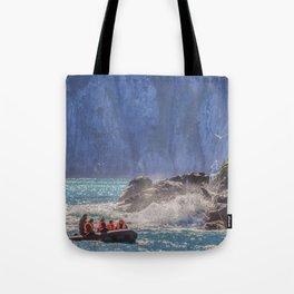 Small boat and waves crashing over rocks Tote Bag