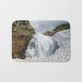 Summer landscape: mountain waterfall falling into snowfield Bath Mat