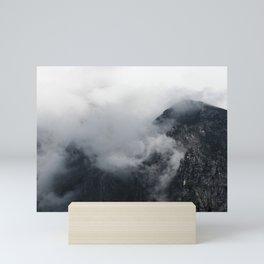 White clouds over the dark rocky mountains Mini Art Print