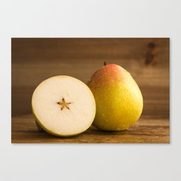 One pear and a half on rustic wood against rustic wooden background close front view Canvas Print