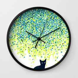 Cat in the garden under willow tree Wall Clock