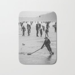 A kid plays ice hockey on a frozen canal. Bath Mat