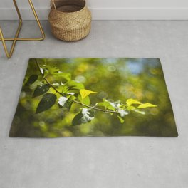 Green leaves and bokeh effect Rug
