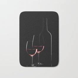 Red wine bottle and two wine glasses on black background on black background Bath Mat