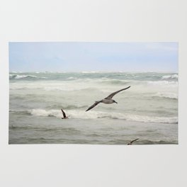 Seagulls flying over rough sea Rug