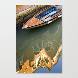 Old boat and old building reflection in water of Venetian channel Canvas Print