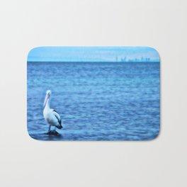 Australian Pelican standing in blue ocean landscape Bath Mat
