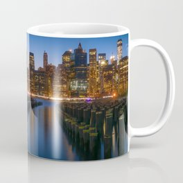 Sea side New York city in the evening with enlighten tall buildings, calm water and blue sky Coffee Mug
