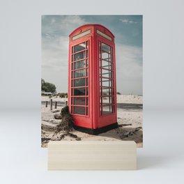 Vintage red telephone box on a sandy beach Mini Art Print
