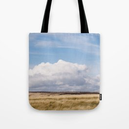 Blue sky and white clouds above sunlit moorland. Derbyshire, UK. Tote Bag