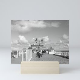 A view up Cromer pier on the Norfolk coast in black and white Mini Art Print