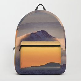 Top in fog. Misty mountains at sunset Backpack