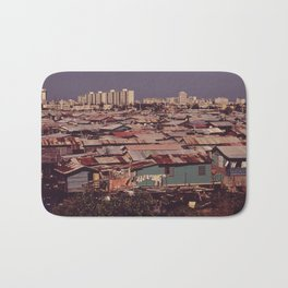 'MODERN BUILDINGS TOWER OVER THE SHANTIES CROWDED ALONG THE MARTIN PENA CANAL' Bath Mat