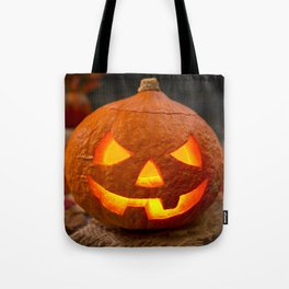 Burning Jack O'Lantern on a rustic table with autumn decorations Tote Bag