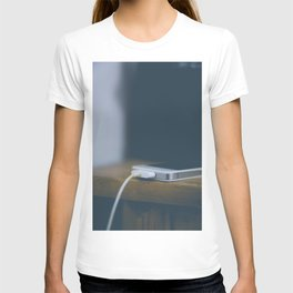 Phone charging on wooden table T-shirt