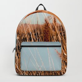 blooming grass flowers with blue sky and mountain background Backpack