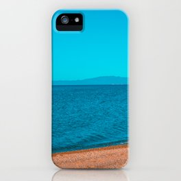 stony beach with mountains in the background iPhone Case