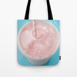 Top view of a strawberry smoothie in a plastic cup with a straw on a blue background. Tote Bag