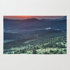 Beautiful sunset behind green fields Rug