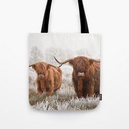 Hairy Scottish highlanders in a natural winter landscape. Tote Bag