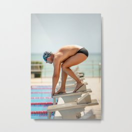 Swimmer in low position ready to jump on starting block in a swimming pool. Metal Print