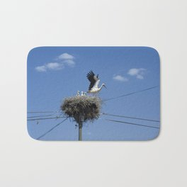 A Stork family in their nest on a telegraph pole. Bath Mat