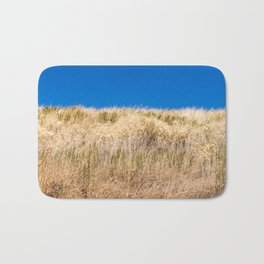 Dry grass meadow and blue sky Bath Mat