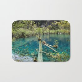 Blue water lake surrounded with greenery Bath Mat