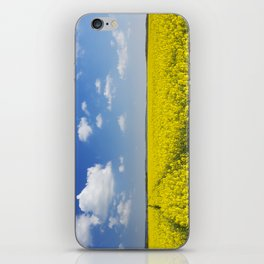 Path through blooming canola under a blue sky with clouds iPhone Skin