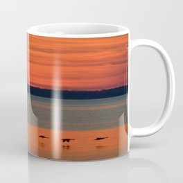 A flock of geese flying north across the calm evening waters of the bay Coffee Mug