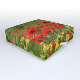 Red poppies on a background of yellow flowers and green grass. Outdoor Floor Cushion