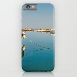 A fishing boat tied up in shallow waters in the city of Lefkada, Greece iPhone Case