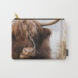 Highland cow feeding on straw on a frosty winters morning. Norfolk, UK. Carry-All Pouch