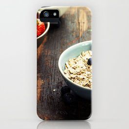 Bowls with cereals and fresh berries on wooden table iPhone Case