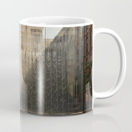 Modern fountain with water splashes on a huge glass window cut by the shadow Coffee Mug